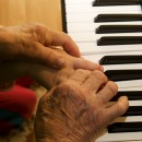 hands of old piano player and grandchild
