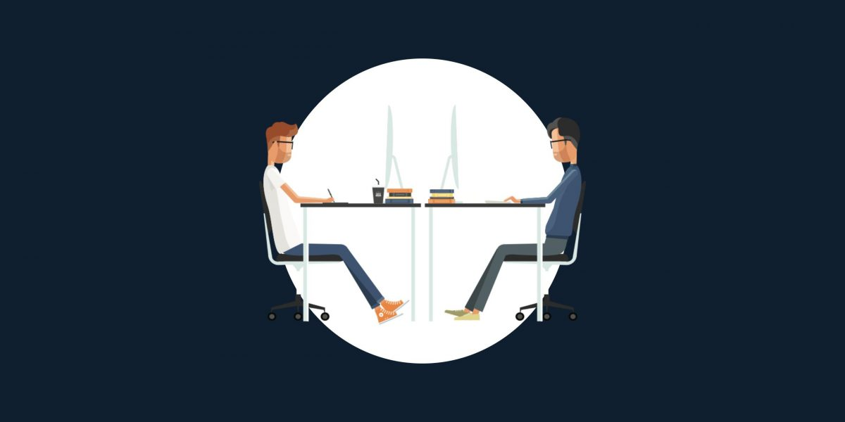 Two men working behind desk