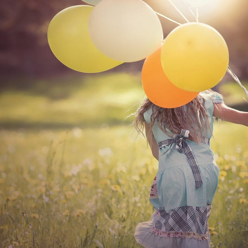 girl with long hair running through field with colourful balloons