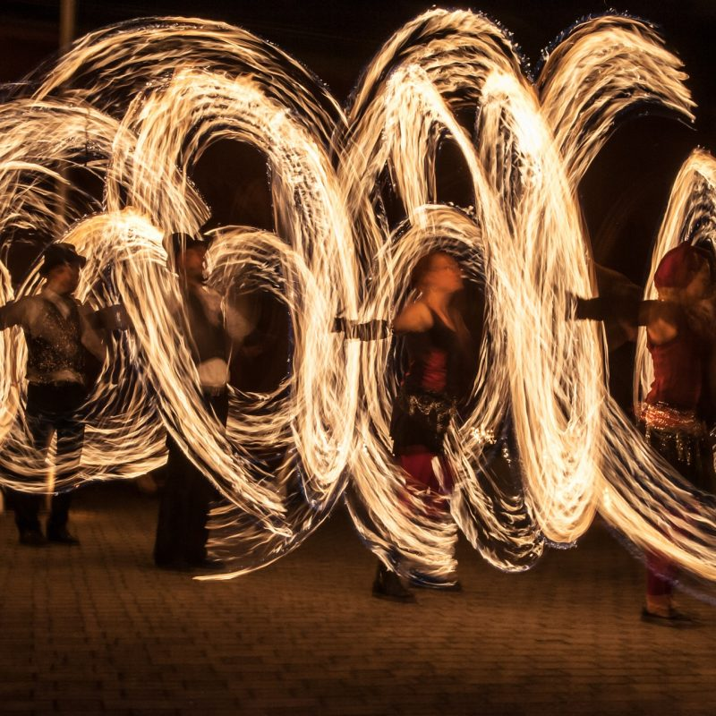 Juggling fire poi dancers