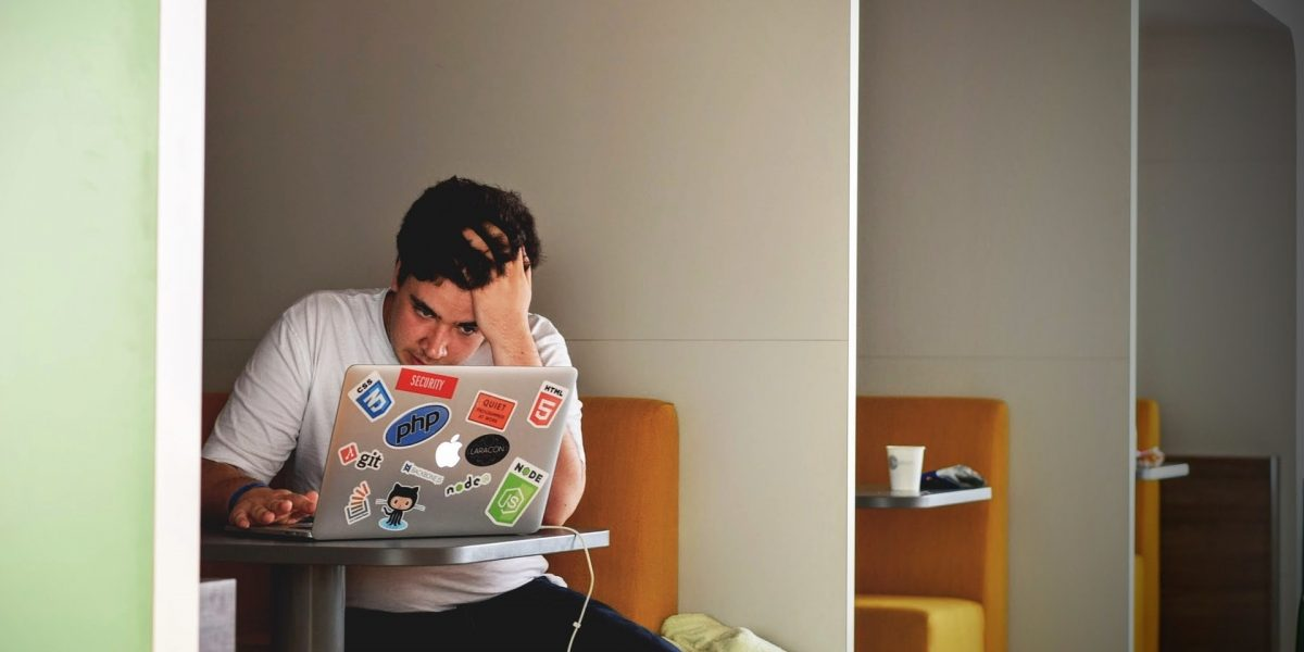 man looking frustrated whilst working on laptop