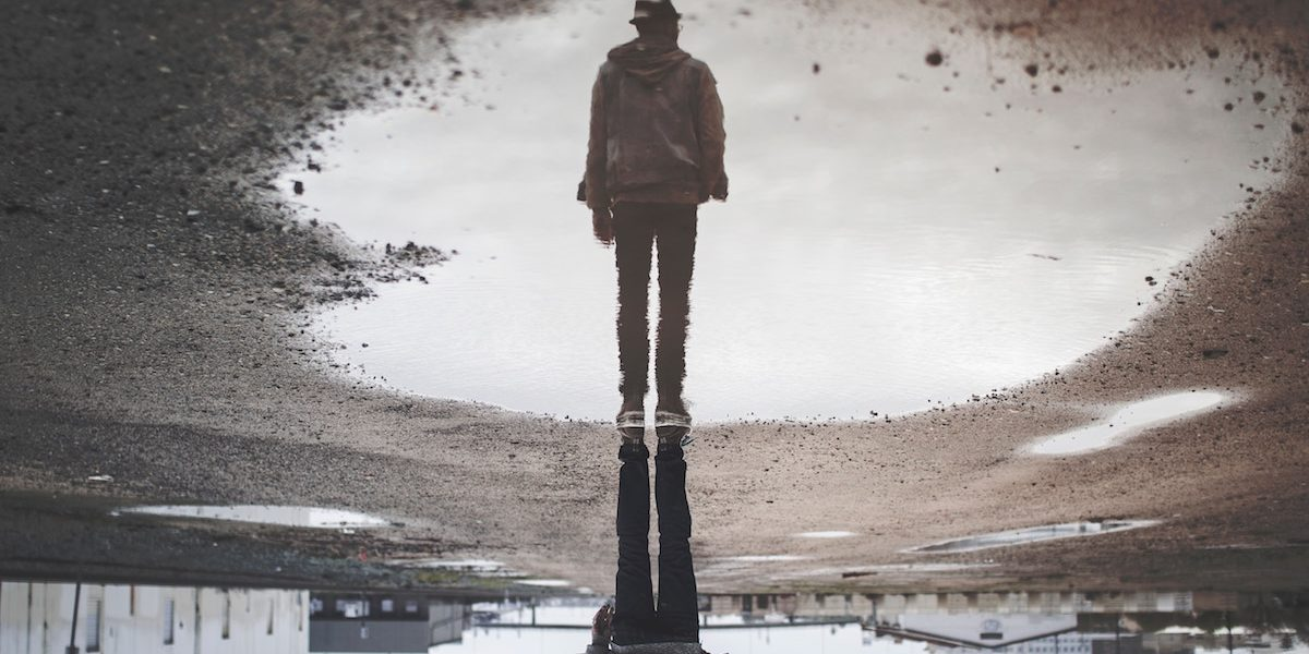 man looking at reflection in large puddle